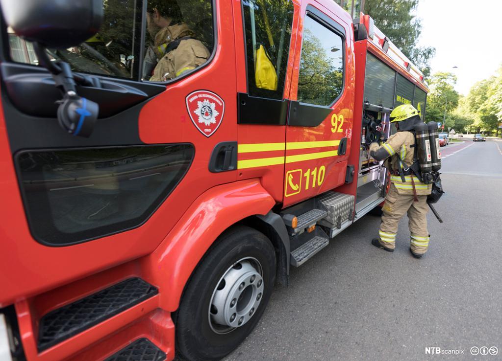 Brannmann og brannbil i aksjon. Foto.