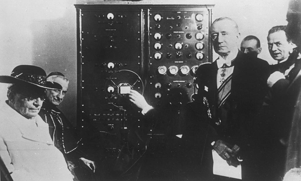 Paven og flere andre menn er samlet for å lytte til Guglielmo Marconis radiosending i 1909. Foto.