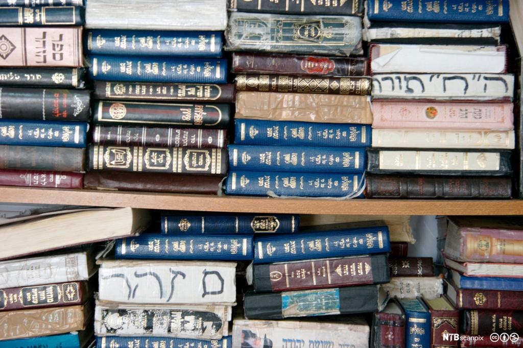 Ulike bøker ligger i bokhylle. Hebraisk tekst. Foto.