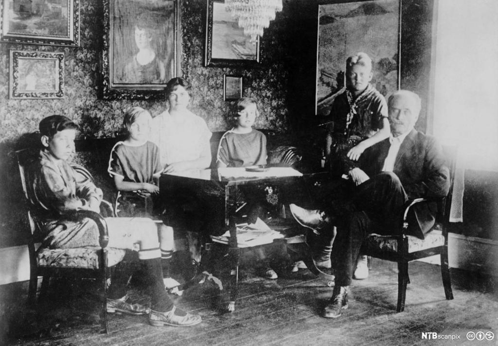 Knut Hamsun med kone og barn sitter rundt e bord i stua på Nørholmen. Fotografi.