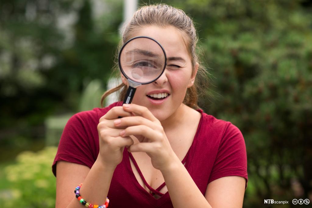 Jente som ser gjennom forstørrelsesglass. Foto