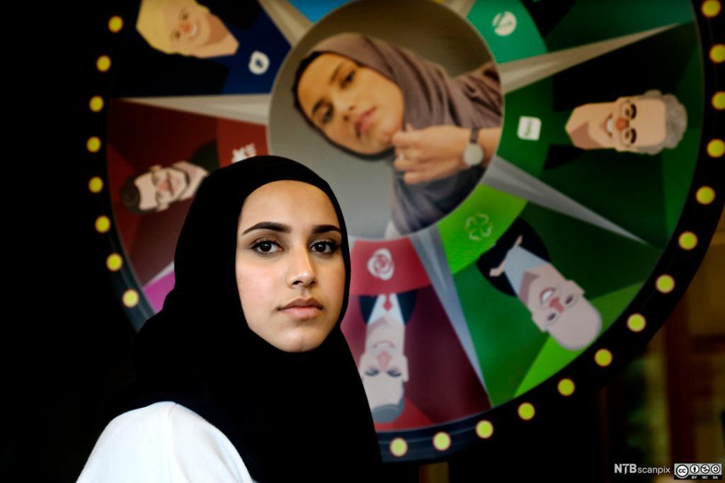 Faten Mahdi Al-Hussaini foran et lykkehjul med bilder av norske politikere. Foto