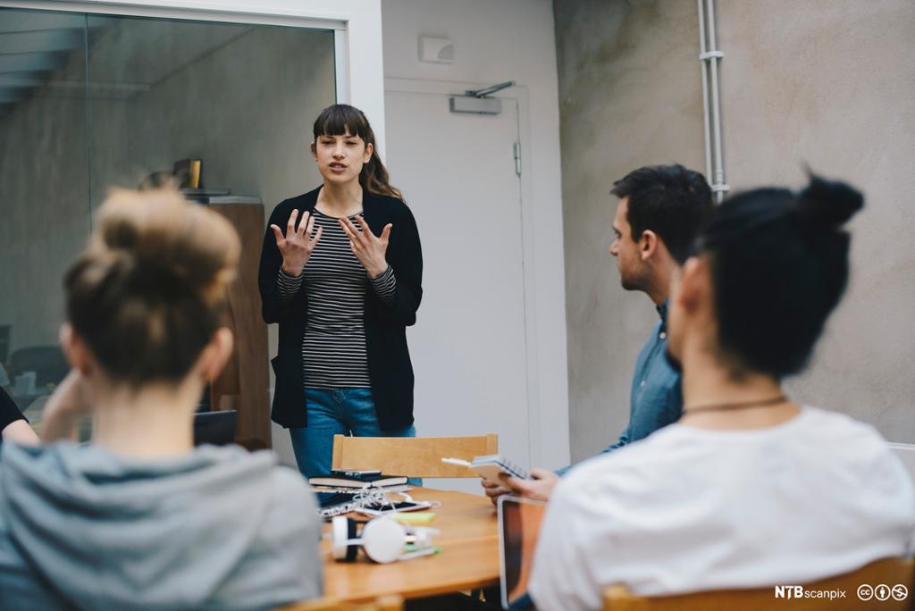 Ei kvinne står og snakker for noen personer som sitter rundt et bord. Hun gestikulerer engasjert. Foto.