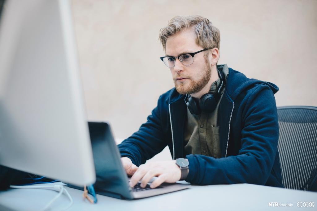 Mannlig dataprogrammerer skriver på laptop. Foto.