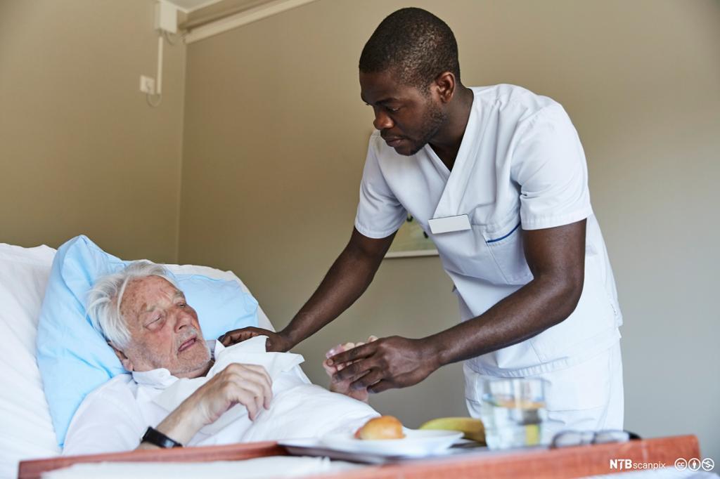 Mannlig sykepleier steller en gammel pasient. Foto.