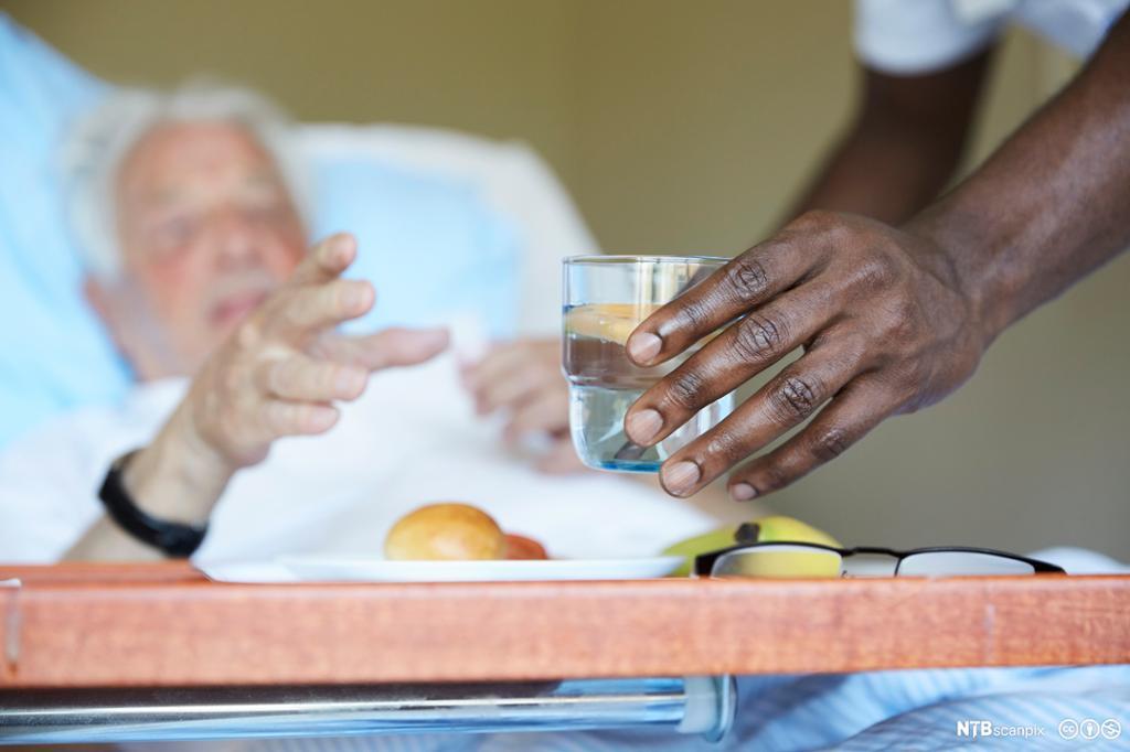 Pleier serverer vann til sengeliggende pasient. Foto