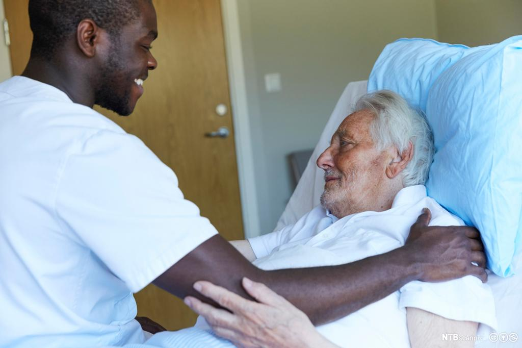 Mannlig sykepleier steller eldre pasient. Foto.