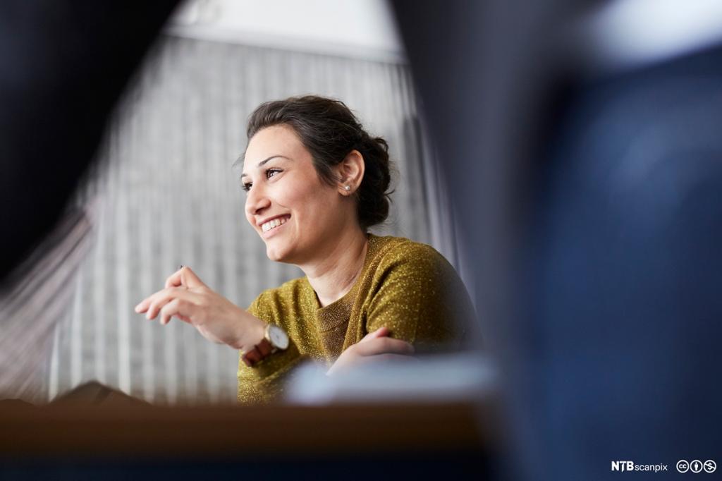 Smilende forretningskvinne på kreativt kontor. Bilde.