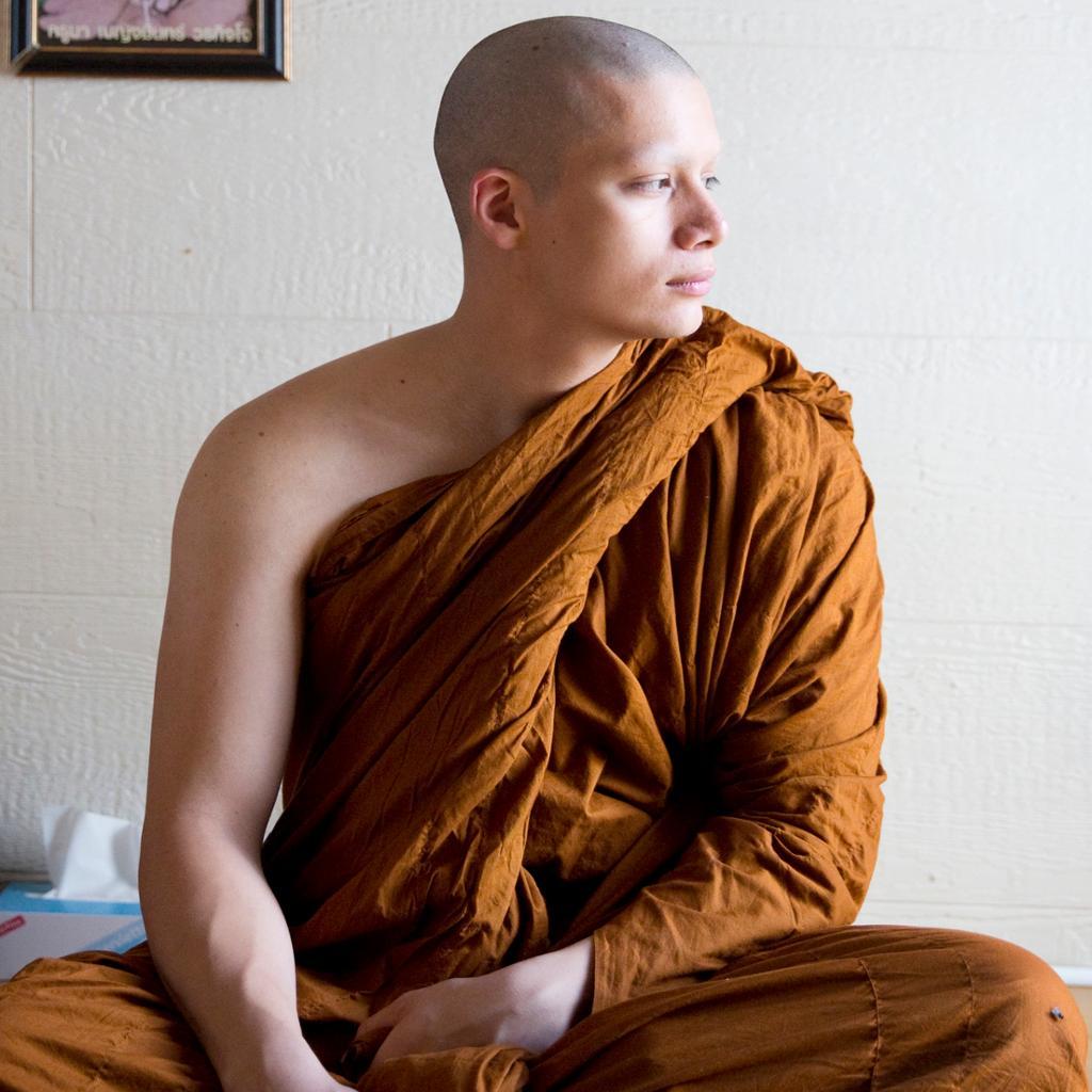 En ung buddhistmunk med gul kjortel stirrer ut av vinduet. Foto.