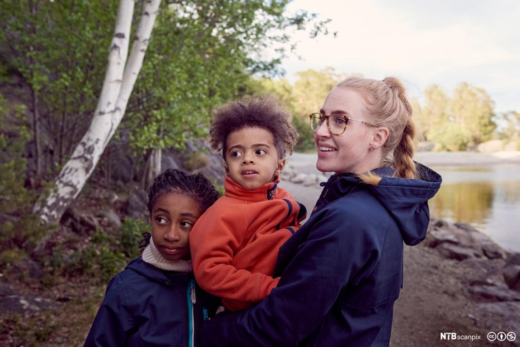 Et fotografi av en kvinne med to barn.