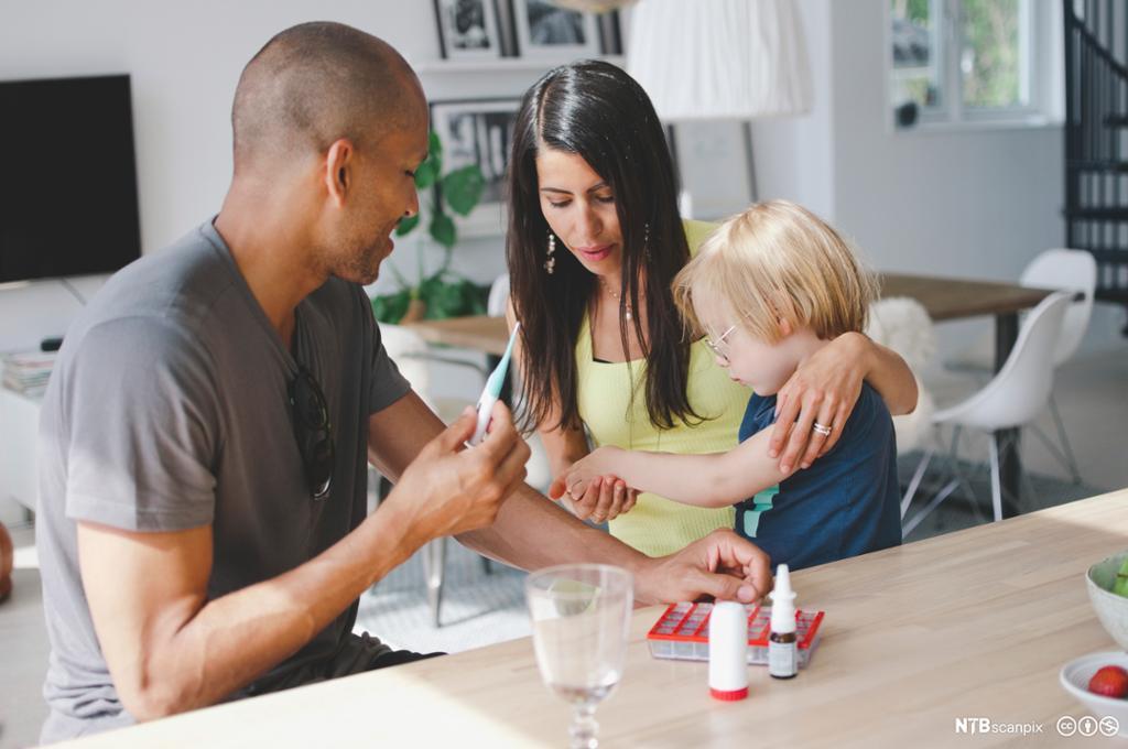 En liten gutt får allergimedisin fra sine foreldre. Foto.