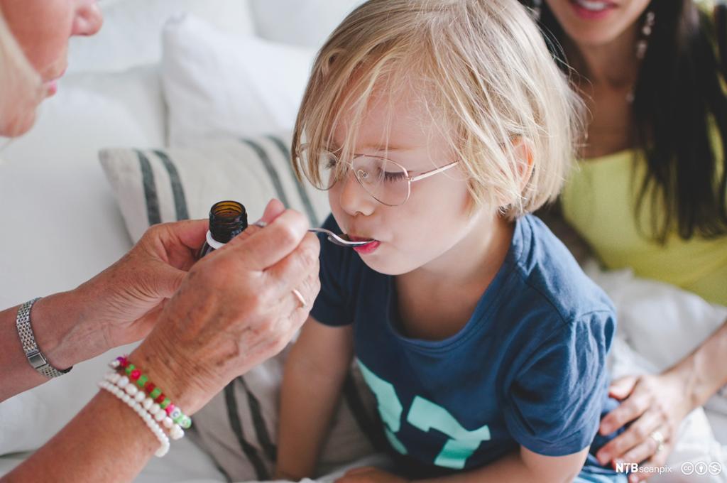 Lyst barn får medisin med teskje. Foto.