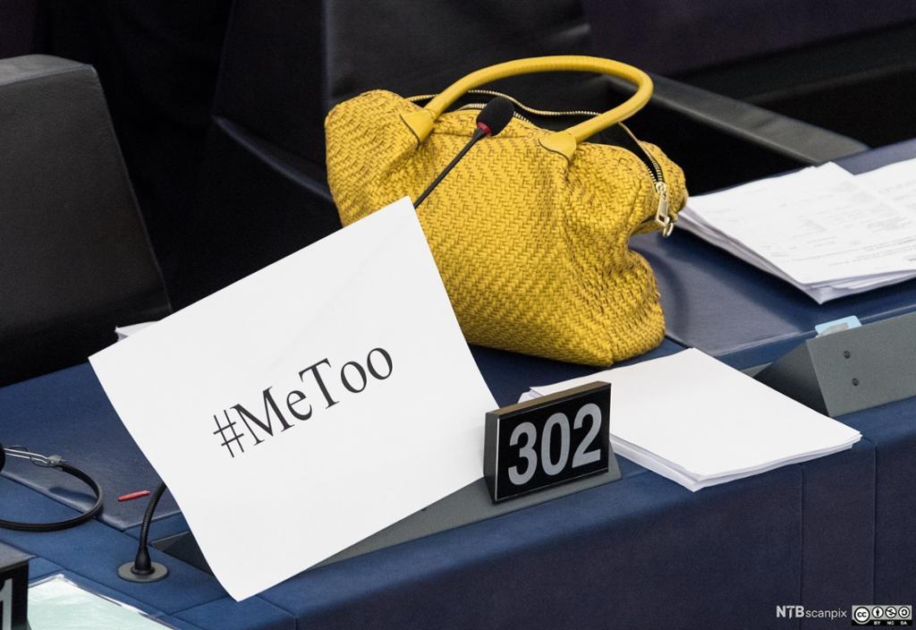 En gul håndveske og en plakar med påskrift Me too. Foto.