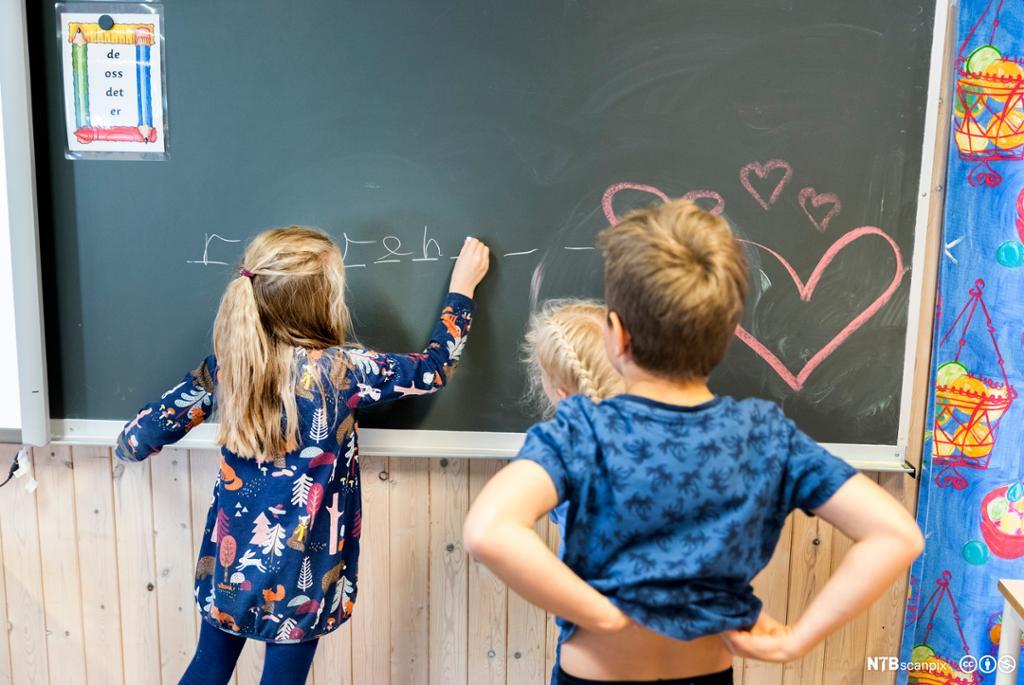 bildet viser ei jente som tegner på tavla