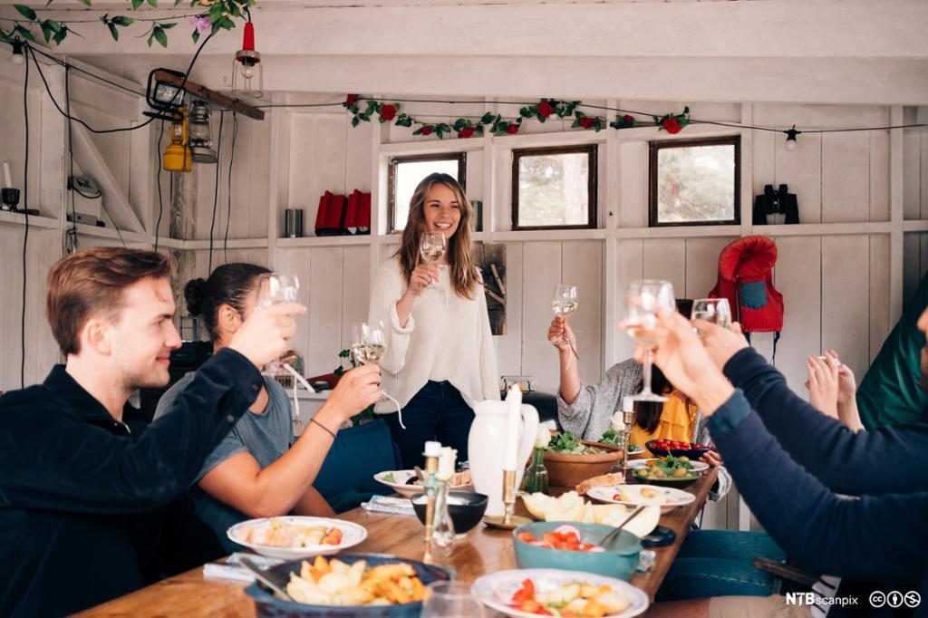 Flere personer rundt et bord dekket med mat, hever glassene og smiler. Foto.