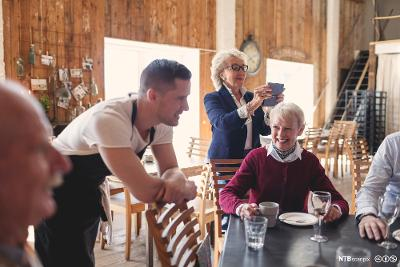 Ung servitør i uformell prat med eldre gjester. foto.