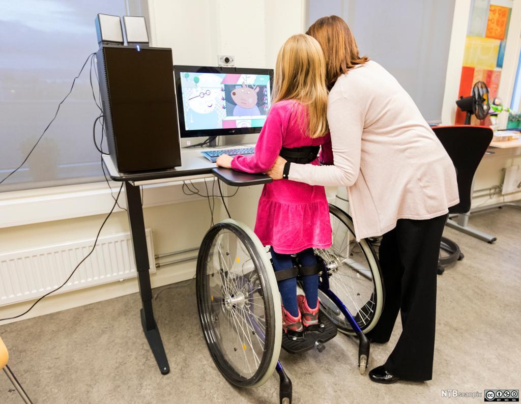 Voksen og barn står ved datamaskin. Foto.