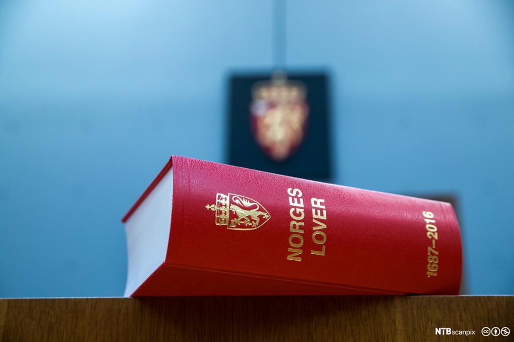 Norges lover ligger på et bord med riksvåpenet på veggen i bakgrunnen. Foto.