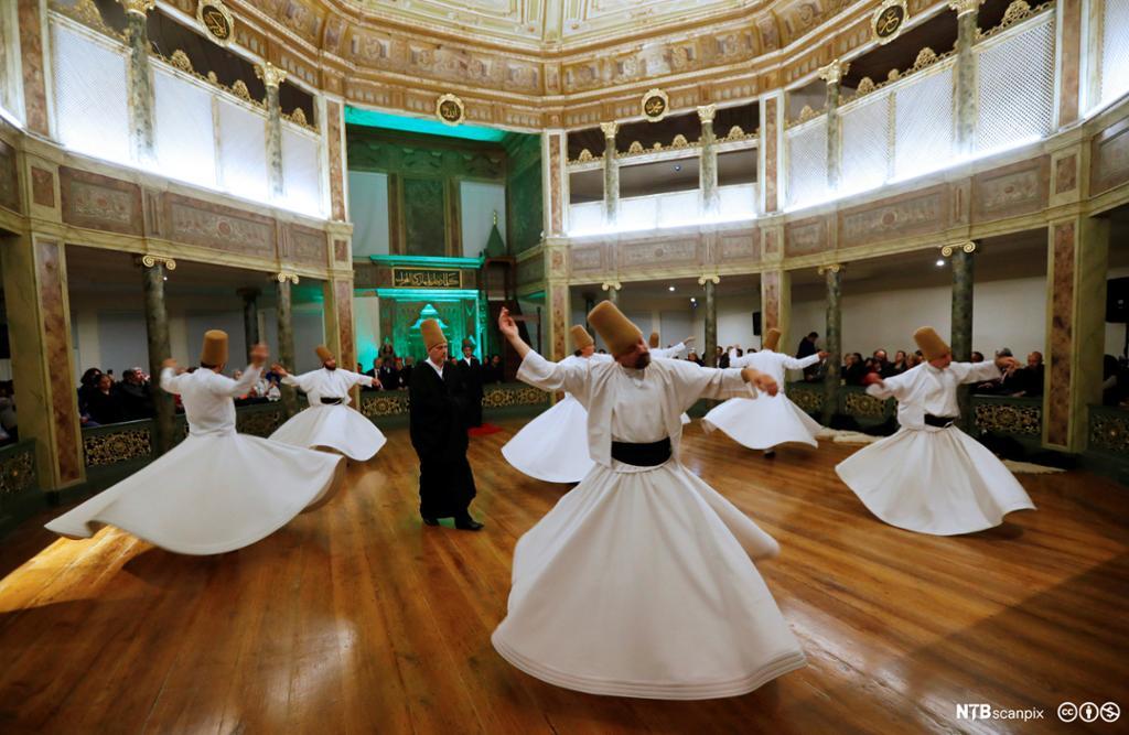 Personar i kvite kjortlar snurrar i heilag dans. Foto.