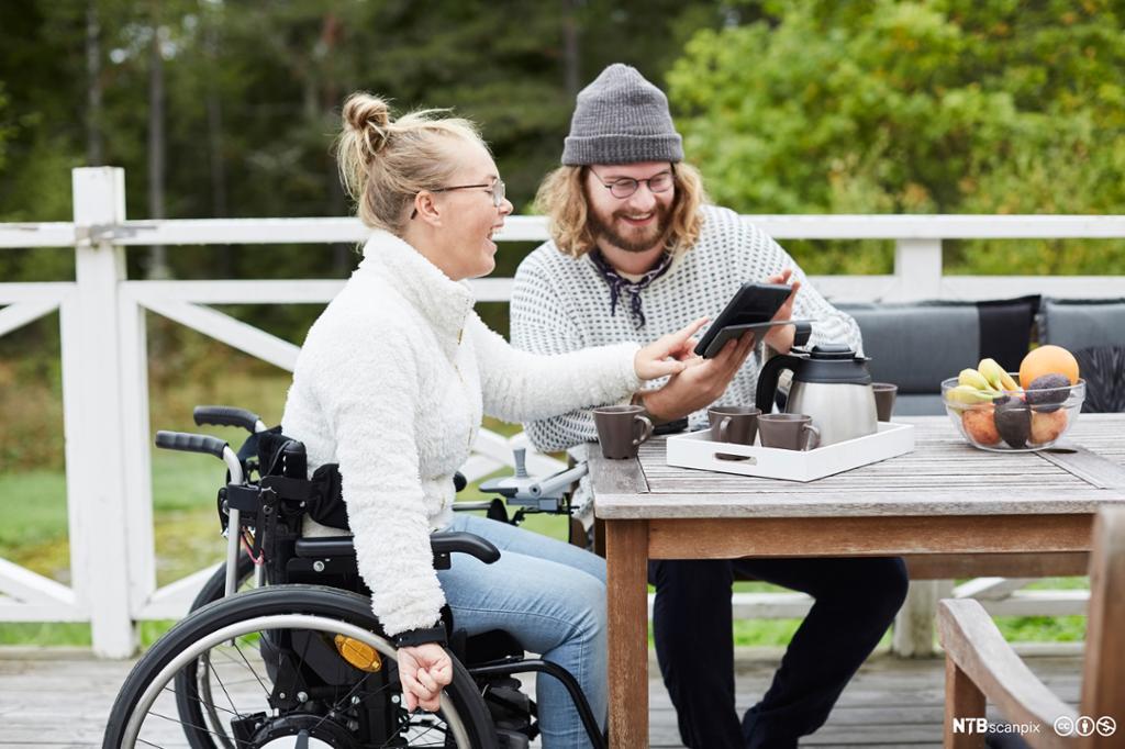 Ung kvinne i rullestol sitter ved hagebord sammen med ung mann. De ser på en skjerm sammen og ler. Foto.