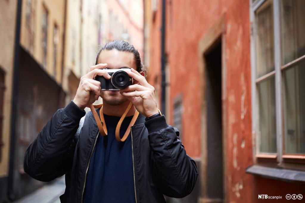 Mann som fotograferer i pittoresk gate. Foto.