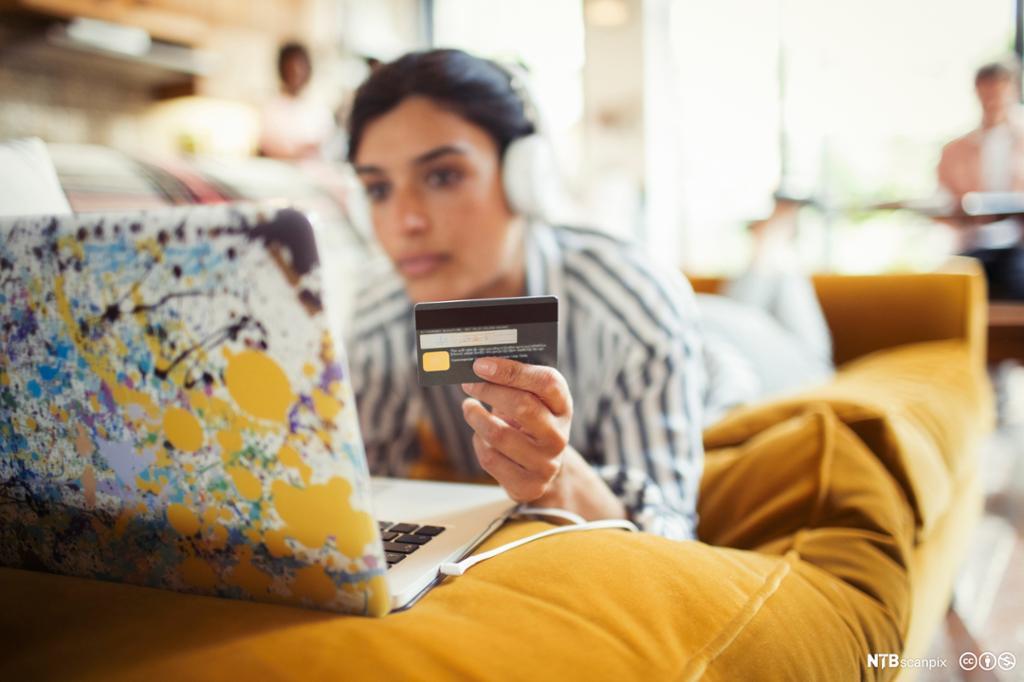 Ung kvinne med hodetelefoner og kredittkort utfører netthandel på laptop. Foto.