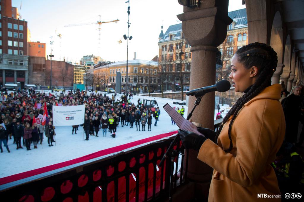 Skuespiller Iselin Shumba taler i mikrofon foran en folkemengde på Youngstorget. Foto.
