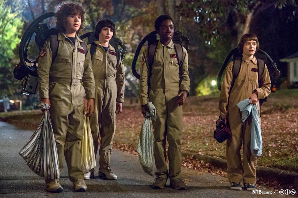 Fire ungdommer går bortover en vei ikledd brune kjeledresser. Foto.