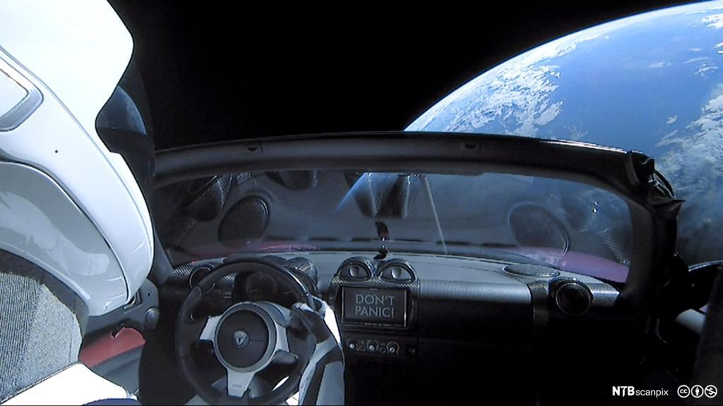 Person i romdrakt kjører bil i verdensrommet med utsikt til jorda. Foto.