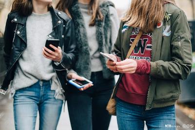 Ungdom med mobiltelefoner i hendene. Foto.