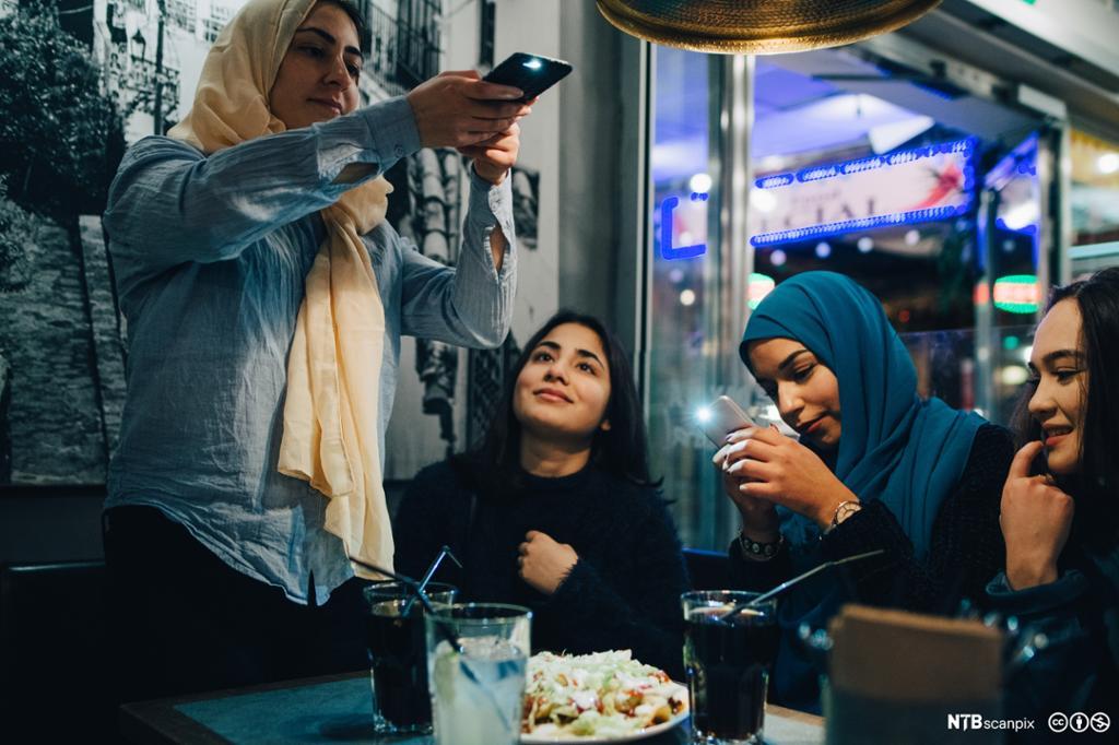 Unge muslimske jenter med hijab på kafe. Foto.