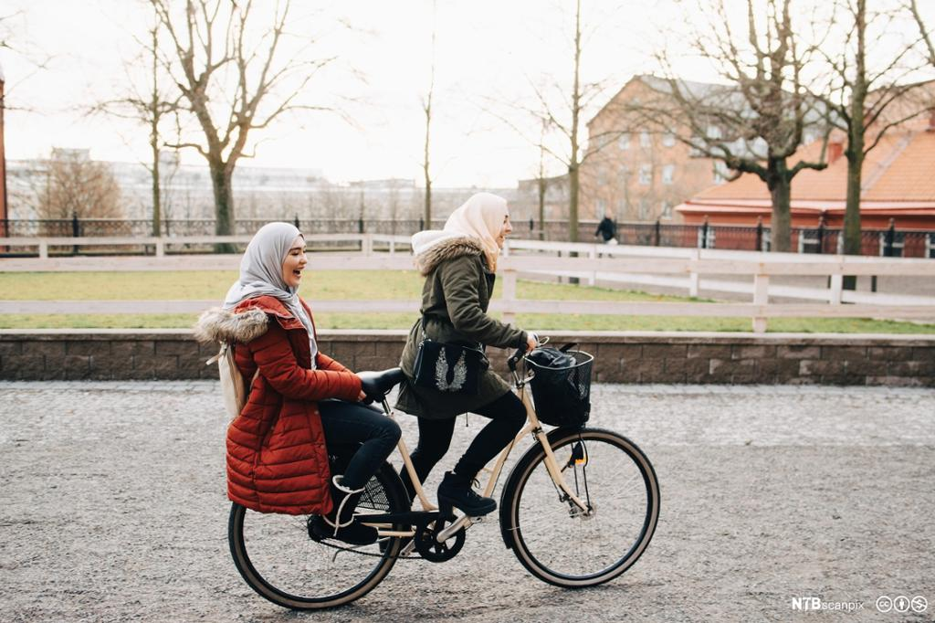 To unge kvinner med hijab på felles sykkel. Foto.