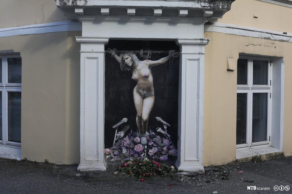 Veggmaleri som viser en kvinnelig politiker som er korfestet. Foran føttene mange mikrofoner og blomster.Maleri.