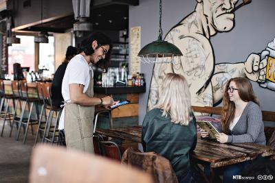 Ein ung servitør på ein kafé tek imot bestilling frå to gjestar. Både han og gjestane smiler. Foto.