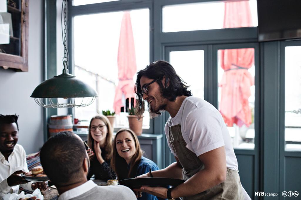 Smilende servitør snakker til fornøyde kunder på restaurant. Foto.