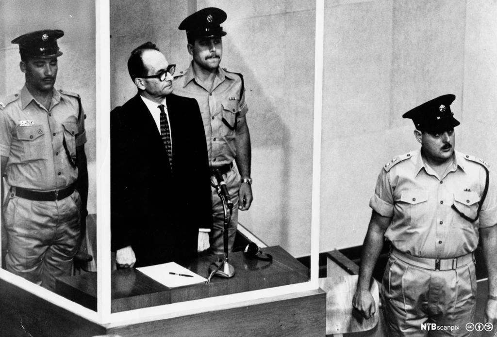 Adolph Eichmann står i en skuddsikker boks i en rettssal. Han er omgitt av tre vakter. Eichmann ble stilt for retten i Jerusalem.