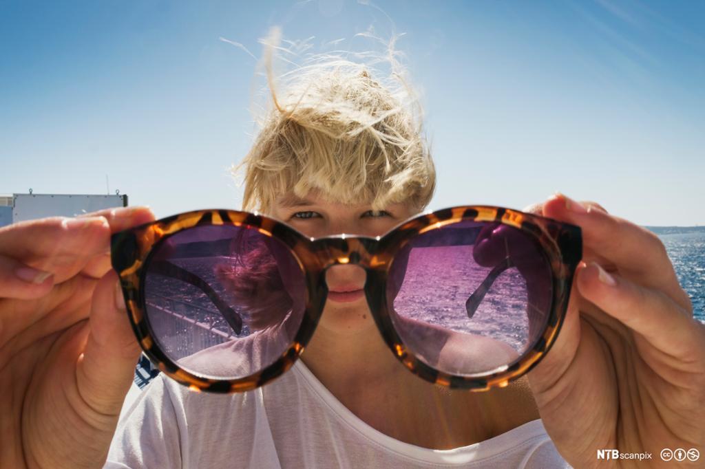 Jente holder opp solbriller foran ansiktet. Foto.
