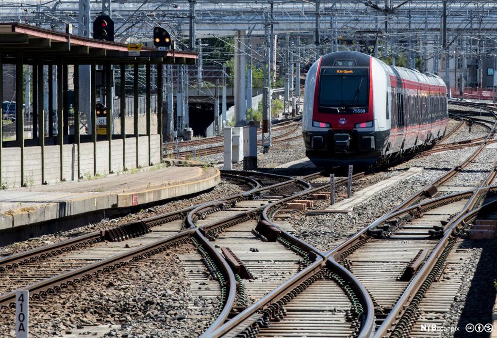 Togskinner med sporveksler og tog på vei inn til stasjonen. Foto.