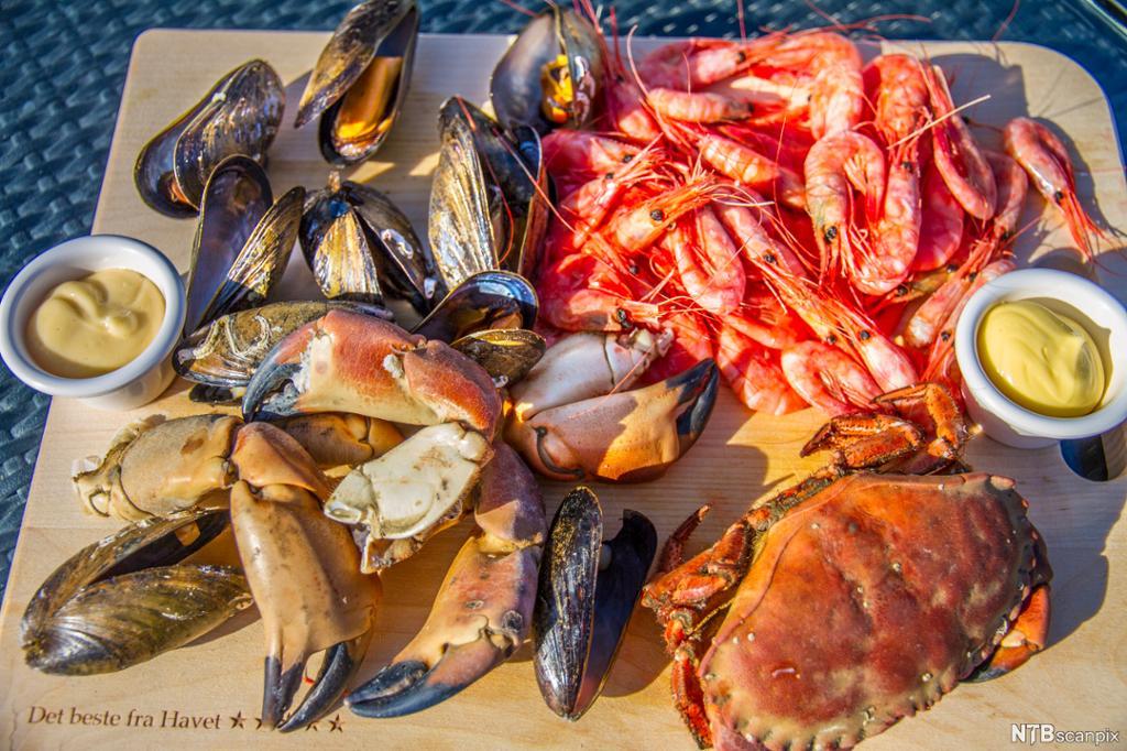 Bord med krabbe, huimmer, reker, blåskjell og majones. Foto.