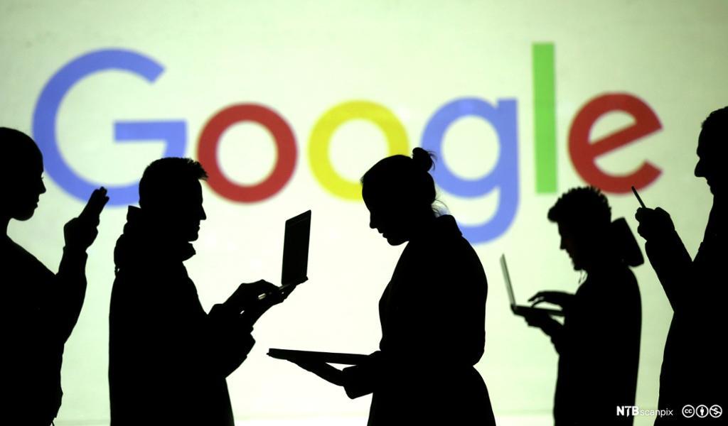 Silhuetter av brukere av bærbare og mobile enheter sett ved siden Google-logo. Foto.