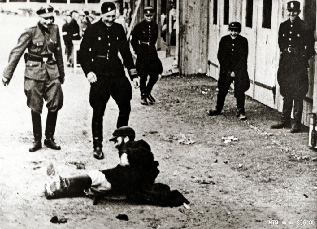 Vakter i uniform står rundt en mann som ligger på bakken. Vaktene ler. Foto.