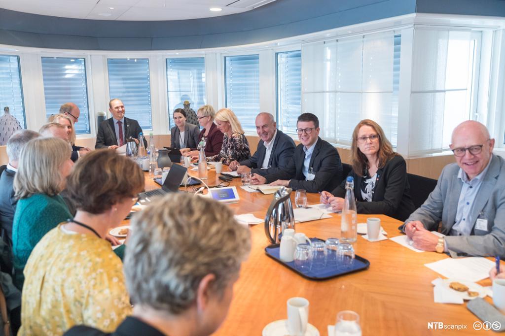 Voksne i ulik alder som sitter rundt et ovalt bord i et stort og lyst møterom. Foto.