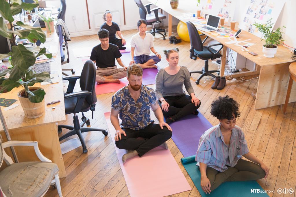 Kolleger sitter på gulvet på kontoret og mediterer. Foto.