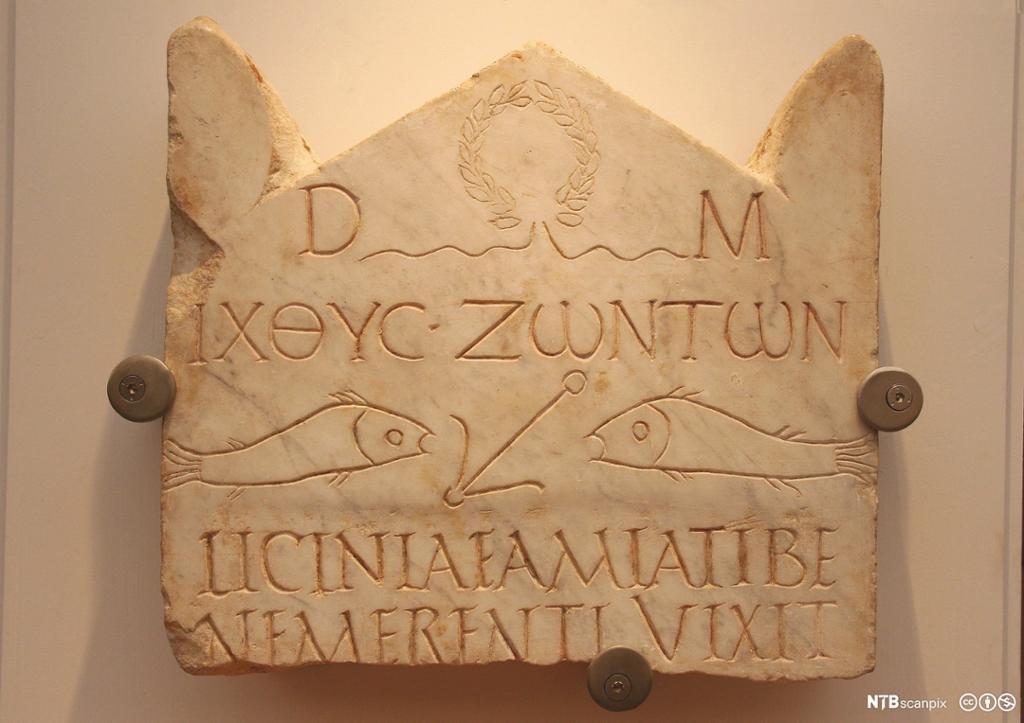 Steintavle henger på en vegg. Gresk tekst. To fisker med en anker i midten. Foto.