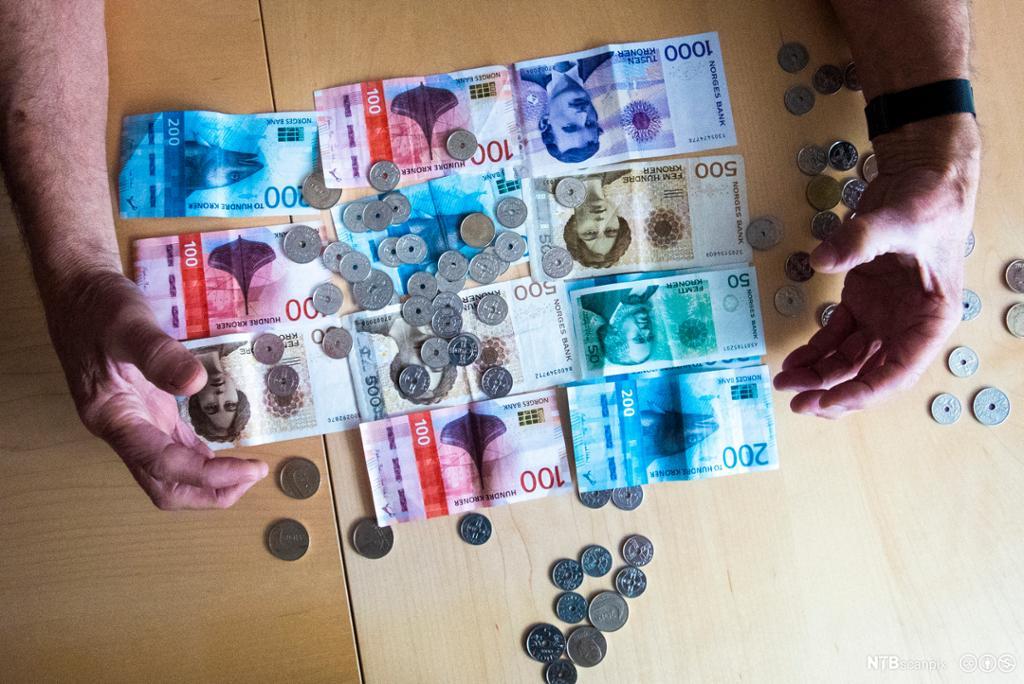 Et fotografi av to hender som samler inn sedler og mynter.
