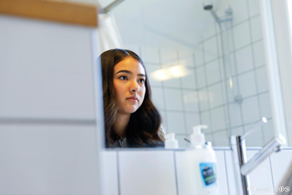 Ung jente står foran speilet på badet. Foto.,