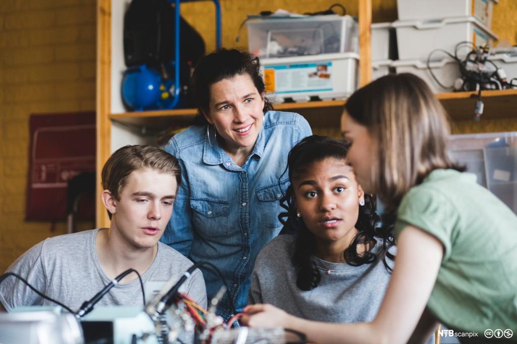 Multi-etnisk gruppe med elever diskuterer mens de gjør et eksperiment i klasserommet. Foto