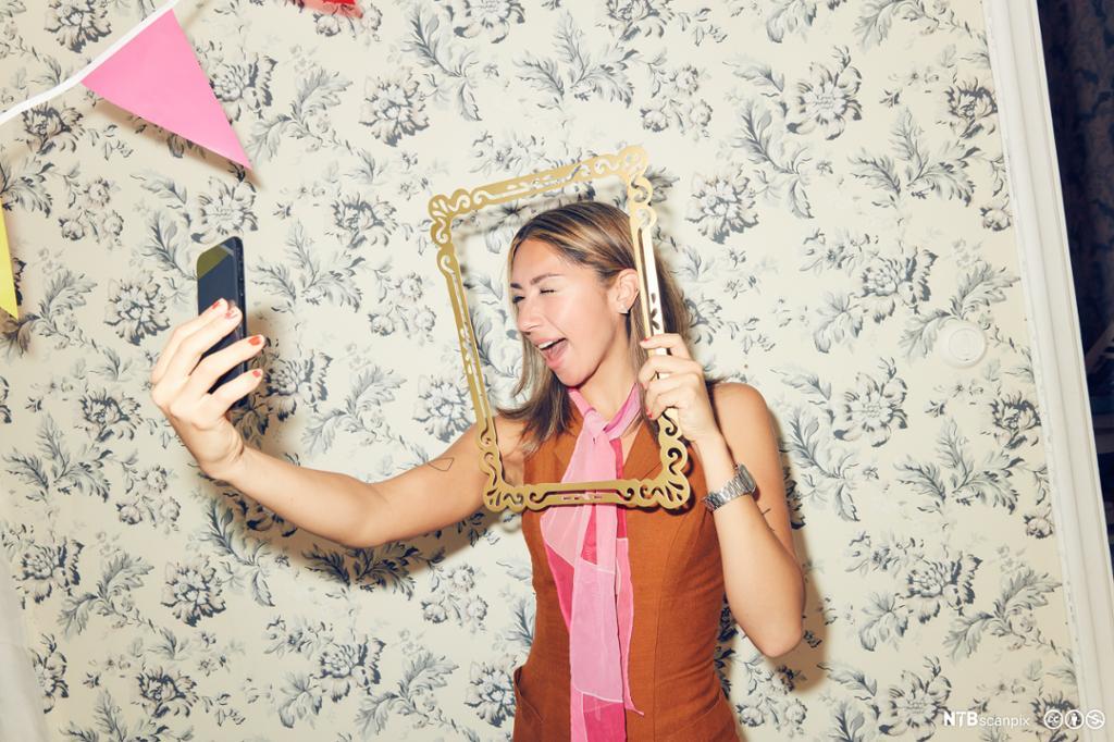 Ung kvinne tar selfie med en smarttelefon. Foto.