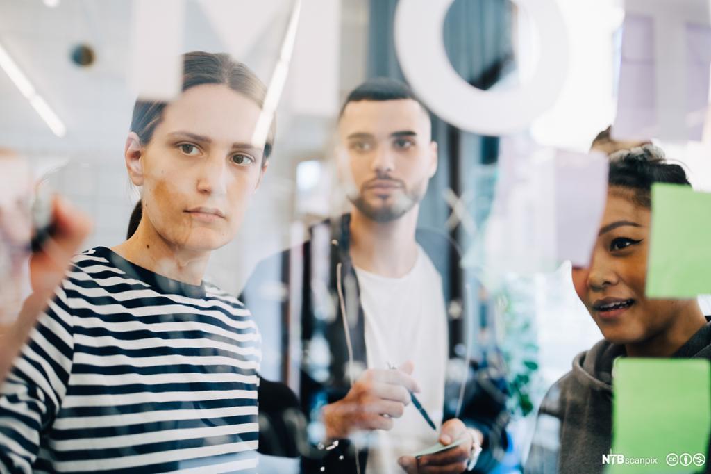 Tre arbeidskollegaer diskuterer strategi. Foto.