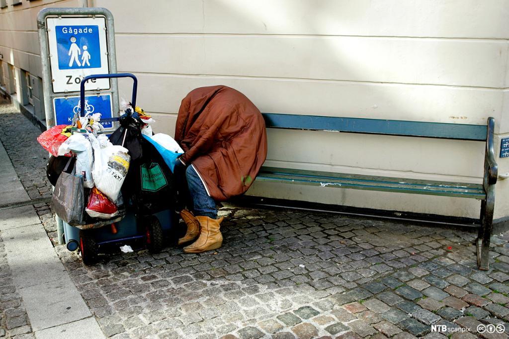 Hjemløs person som sitter på en benk i et bymiljø og som har med seg alle eiendelene sine på ei tralle. Foto.